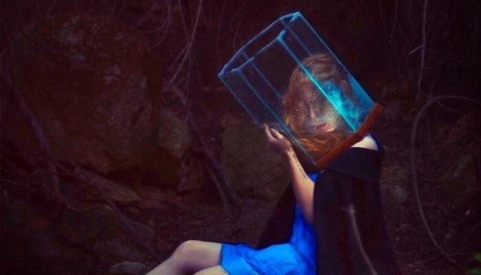 Frau im blauen Kleid trägt einen Wasserbehälter über den Kopf gestülpt