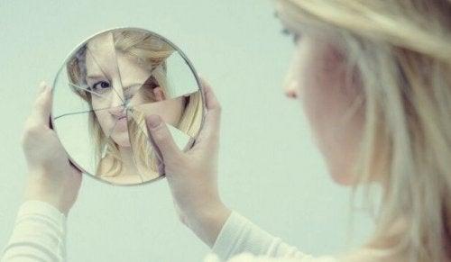 Frau schaut in einen zerbrochenen Spiegel als Symbol für die Fallen des Egos