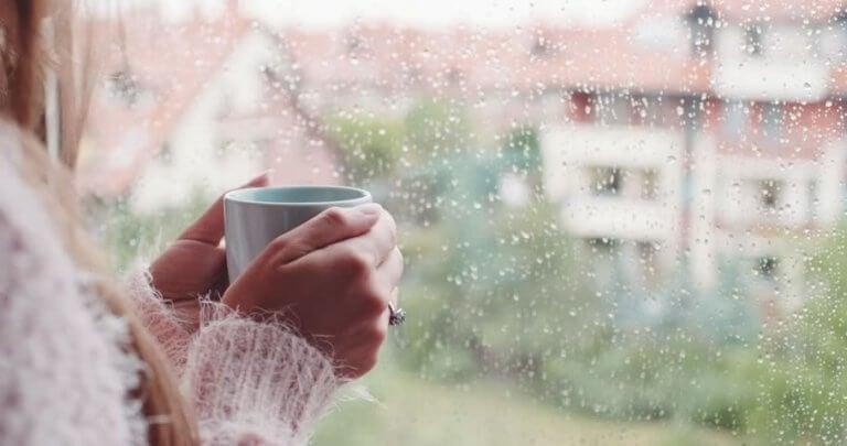 Frau trinkt Tee vor einem Fenster, auf das Regen fällt