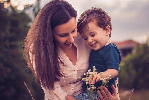 Mutter und Sohn schauen sich eine Blume an