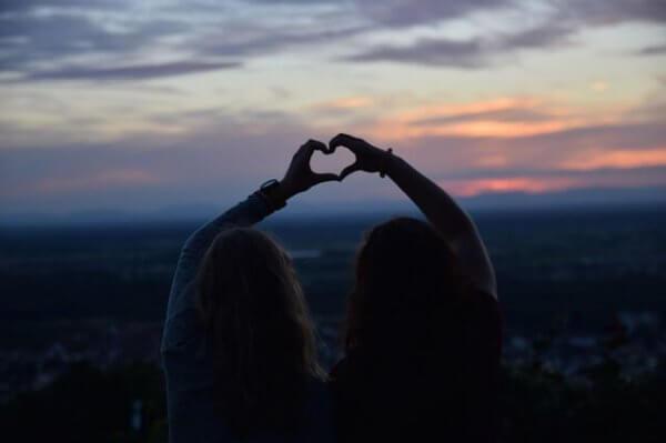 Zwei Freunde bedeuten ein Herz mit ihren Händen.