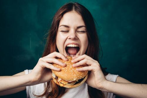 Frau isst nachts einen Hamburger