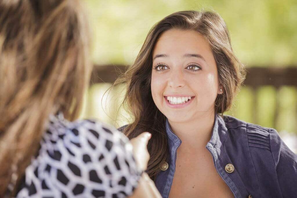 Frau lacht während eines Gesprächs mit ihrer Freundin