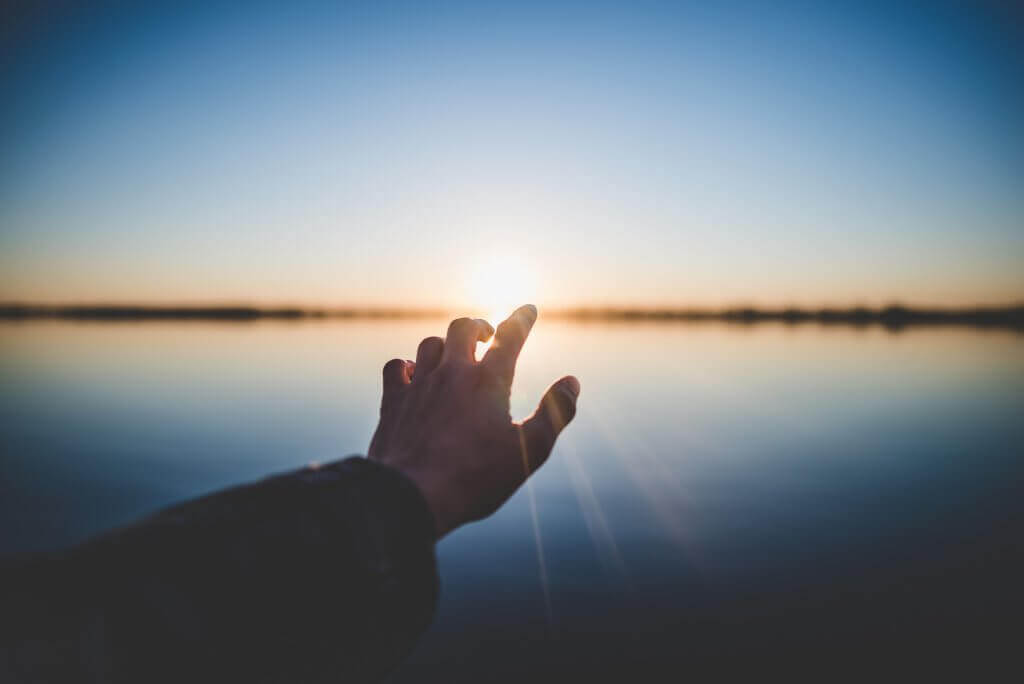 Hand, die die Sonne berührt