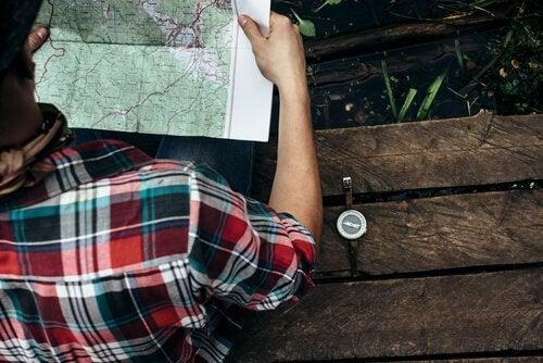 Junge mit kariertem Hemd sitzt auf einer Bank und betrachtet eine Landkarte.