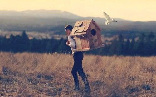 Junge trägt Vogelhaus auf dem Rücken