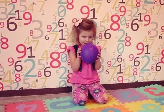 Ein Mädchen in einer Spielecke hält einen Ballon in seinen Händen.
