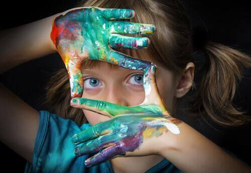 Kind formt mit angemalten Händen einen Rahmen