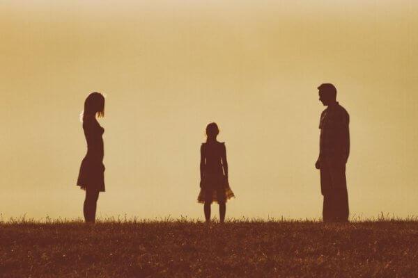 Ein Kind steht zwischen seinen Eltern.
