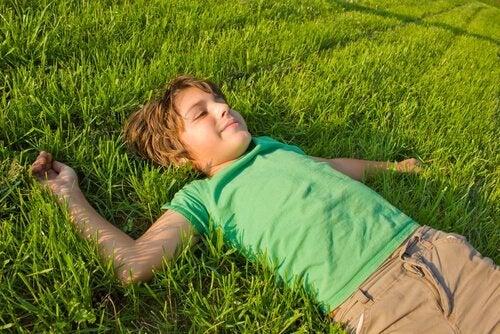 Ein Junge liegt entspannt auf einer Wiese.