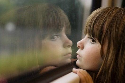 Ein Mädchen schaut aus einem Fenster.