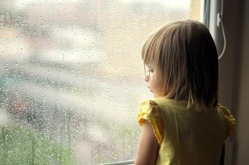 Kleines Mädchen schaut nachdenklich aus einem Fenster