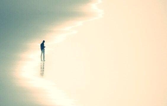 Ein Mann steht allein am Strand.