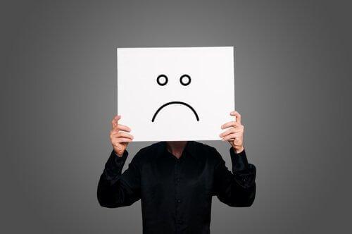 Ein Mann hält sich ein Blatt Papier vor sein Gesicht, worauf ein trauriges Icon zu sehen ist.