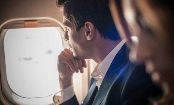 Ein Mann starrt aus einem Flugzeugfenster.