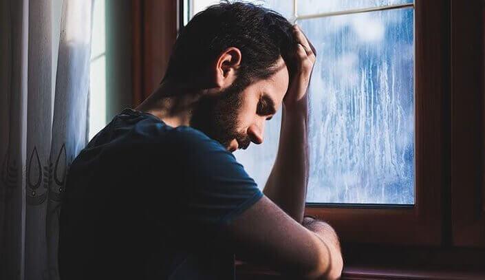 Ein Mann sitzt mit gesenktem Kopf am Fenster