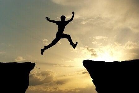 Ein Mann springt über eine Klippe
