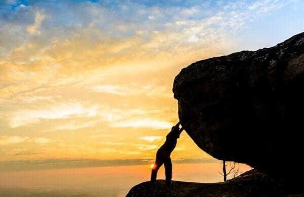 Ein Mann stützt sich an einem Felsen ab.