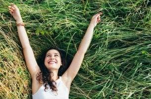 Eine glückliche und optimistische Frau liegt im Gras.