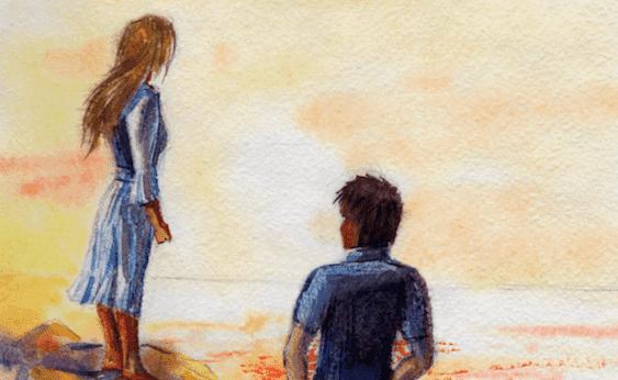 Paar steht gemeinsam am Strand und schaut aufs Meer