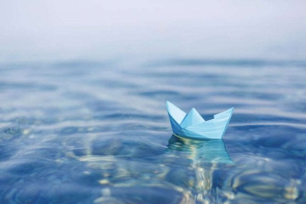 Schiff aus Papier, das auf dem Wasser schwimmt