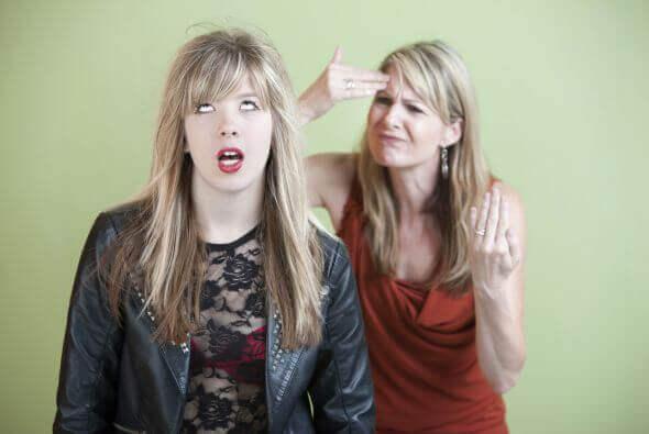 Ein Mädchen schaut genervt, während ihre Mutter es ausschimpft.