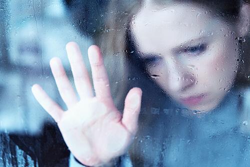 Traurige Frau legt ihre Hand an Fensterscheibe
