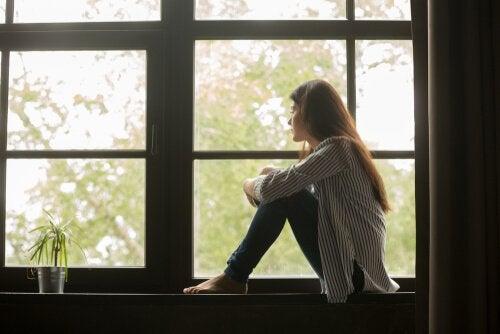Traurige Frau sitzt beim Fenster