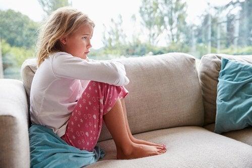 Ein trauriges Mädchen versteht die Doppelbindung ihrer Eltern nicht.