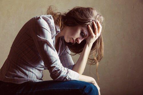 Frau stützt verzweifelt ihren Kopf auf ihren Arm