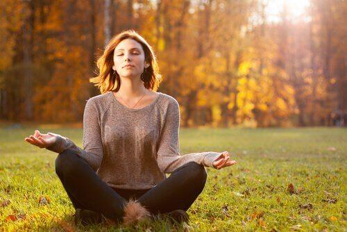 Eine Frau praktiziert Yoga in einem Wald.