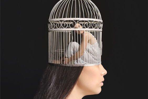 Frau sitzt ängstlich in einem Käfig