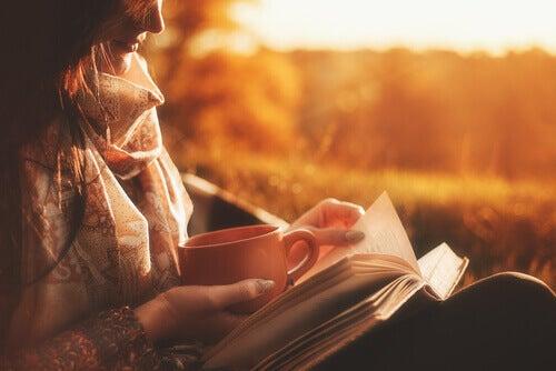 Frau trinkt Tee und liest ein Buch