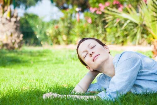Frau liegt entspannt auf einer Wiese