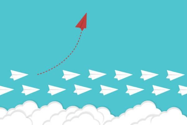 Viele weiße Papierflieger mit einem roten, nach oben ausweichenden Papierflieger
