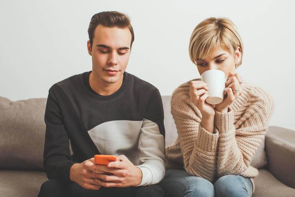 Frau schaut ihrem Partner über die Schulter auf sein Handy