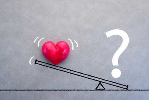 Ein Herz und ein Fragezeigen auf einer Waage