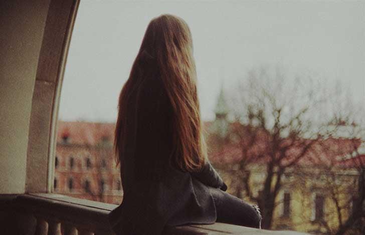 Frau sitzt allein auf einem Balkongeländer