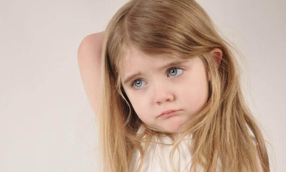 Kleines trauriges Mädchen mit blonden Haaren