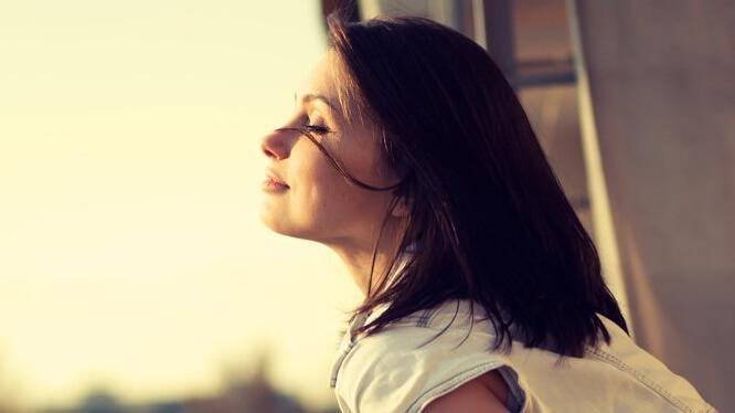 Frau mit geschlossenen Augen atmet frische Luft ein