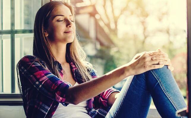 Lächelnde Frau sitzt mit geschlossenen Augen am Fenster