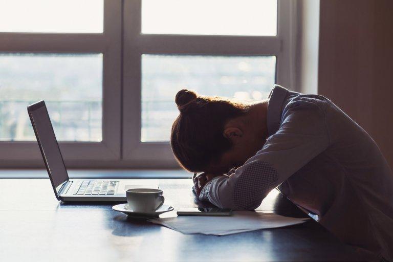 Junge Frau sitzt erschöpft an ihrem Arbeitsplatz