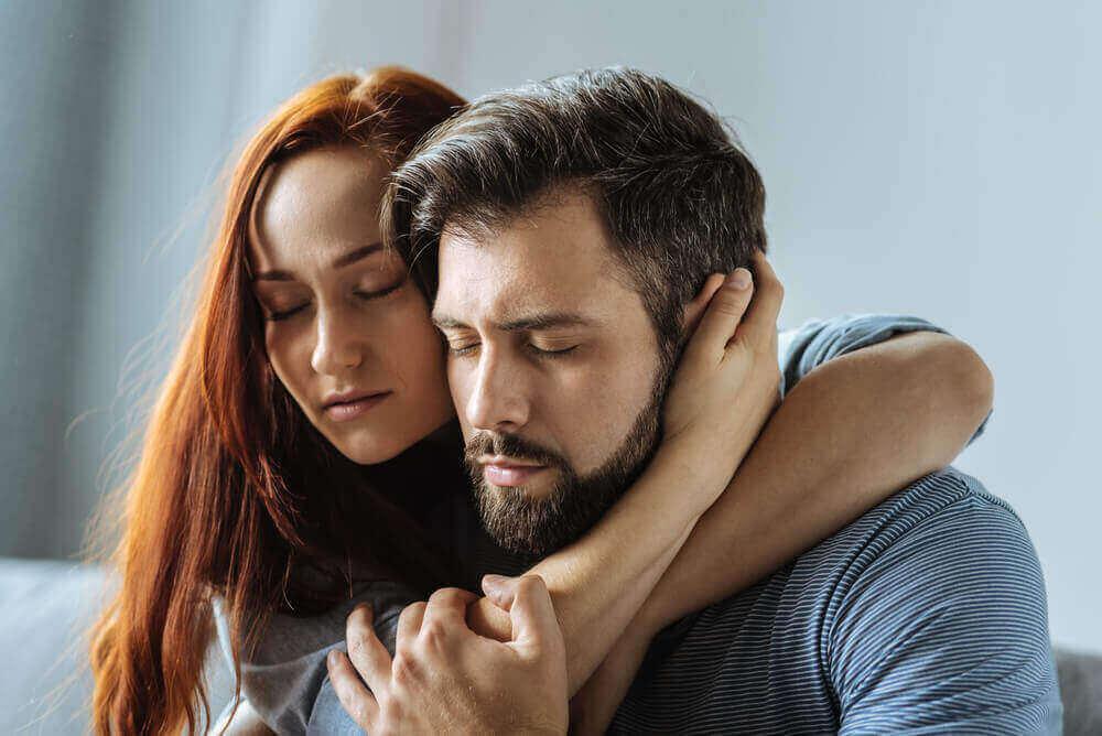 Frau, die einen Mann mit geschlossenen Augen umarmt