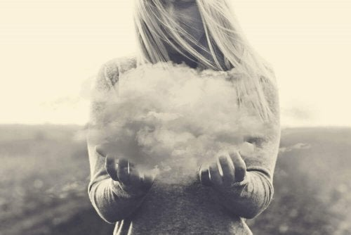 Frau hält eine Wolke fest, die negative Gedanken repräsentiert