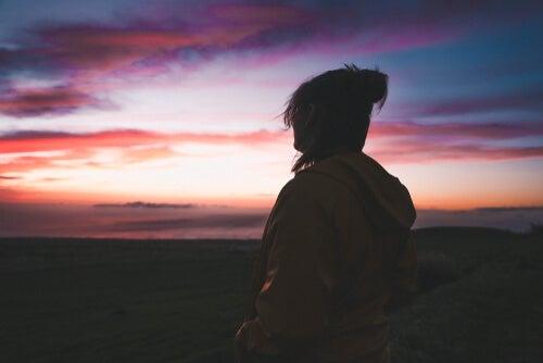 Frau sieht sich allein im Morgengrauen den Himmel an