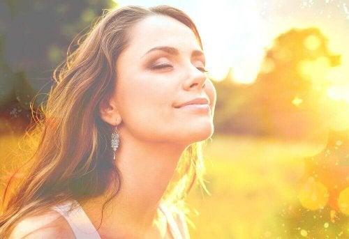 Frau lächelt mit geschlossenen Augen, als Symbol für das Fließenlassen