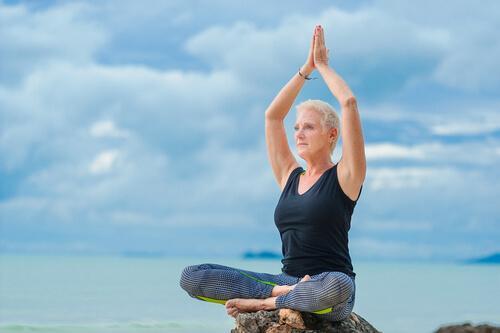 Frau in fortgeschrittenem Alter praktiziert Yoga am Meer