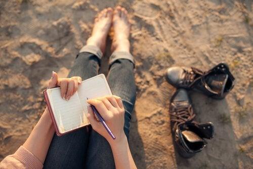 Frau schreibt am Strand