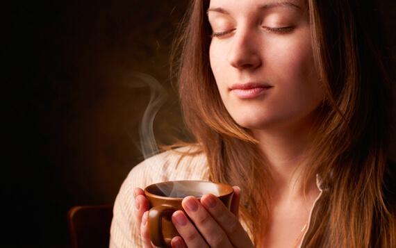 Frau mit geschlossenen Augen genießt den Geruch von Kaffee