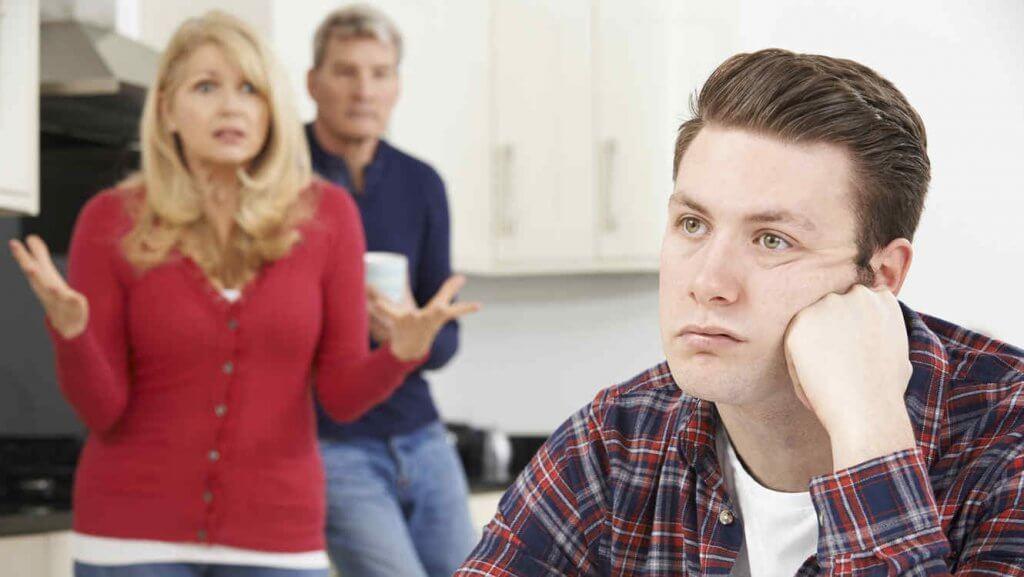 Eltern diskutieren in der Küche mit ihrem erwachsenen Sohn